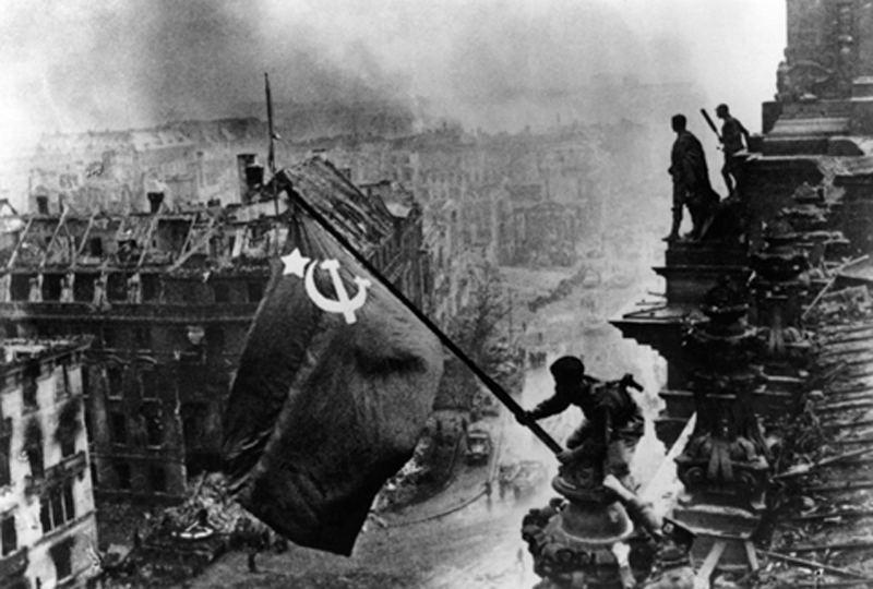 Raising a flag over the Reichstag by Yevgeny Khaldei – Iconic Photograph
