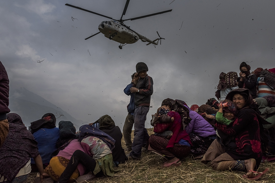 3—Gumda, Nepal. Saturday, May 09, 2015: Nepalese villagers look on as they watch a helicopter picking up a medical team, dropping aid at the edge of a makeshift landing zone on May 9, 2015 in the village of Gumda, Nepal. On the 25th of April, just before noon local time, as farmers were out in fields and people at home or work, a devastating earthquake struck Nepal, killing over 8,000 people and injuring more than 21,000 according to the United Nations Office for the Coordination of Humanitarian Affairs. Homes, buildings and temples in Kathmandu were destroyed in the 7.8 magnitude quake, which left over 2.8 million people homeless, but it was the mountainous districts away from the capital that were the hardest hit. Villagers pulled the bodies of their loved ones from the rubble by hand and the wails of grieving families echoed through the mountains, as mothers were left to bury their own children. Over the following weeks and months, villagers picked through ruins desperate to recover whatever personal possessions they could find and salvage any building materials that could be reused. Despite relief teams arriving from all over the world in the days after the quake hit, thousands of residents living in remote hillside villages were left to fend for themselves, as rescuers struggled to reach all those affected. Multiple aftershocks, widespread damage and fear kept tourists away from the country known for its searing Himalayan peaks, damaging a vital climbing and trekking industry and compounding the recovery effort in the face of a disaster from which the people of Nepal continue to battle to recover.