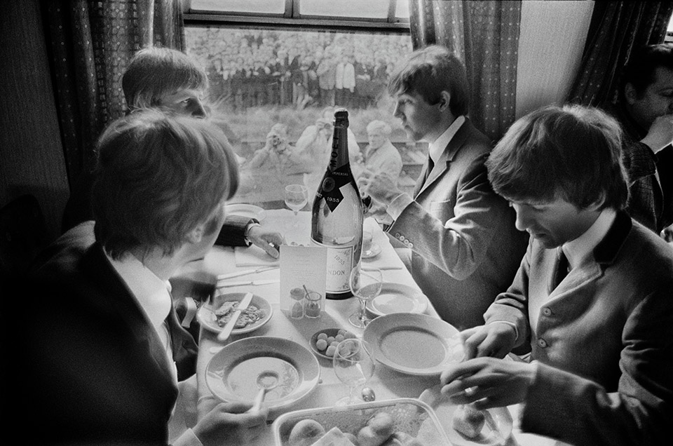 G.B. ENGLAND. LONDON. The BEATLES during filming of 'A Hard Days Night'. John, Paul, George and Ringo take time off, during the making of the film 'A Hard Days Night', for a meal on the train. Thousands of fans lined the route. 1964.