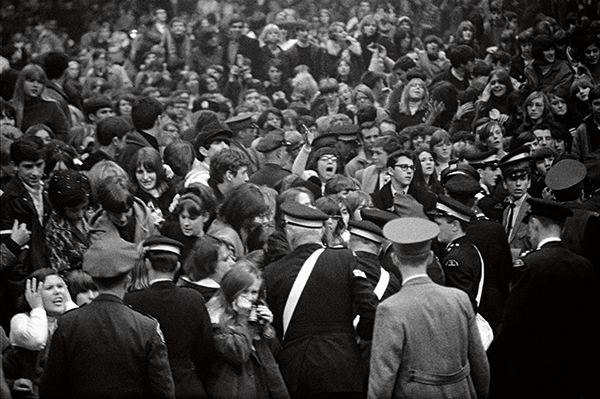 Crowds of fans held back by police, by Gered Mankowitz © Bowstir Ltd/Gered Mankowitz