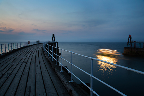 Streaks of light created by a boat leaving Whitby Pier made for a pleasing shot