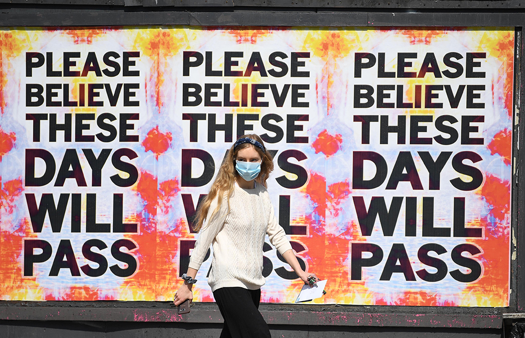 """street photograph, girl infront of colourful posters that say """"please believe these days will pass"""""""