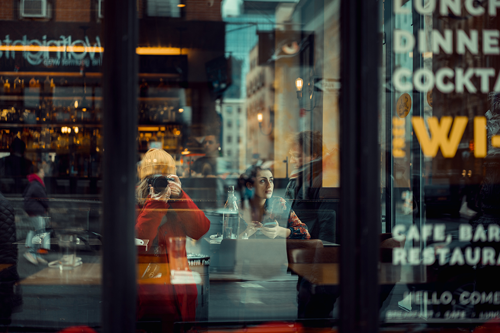 Paola taking a photograph of a coffee shop window