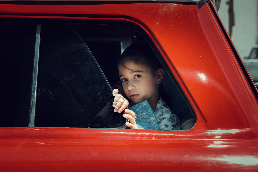 Image of a young girl looking out a bright red car
