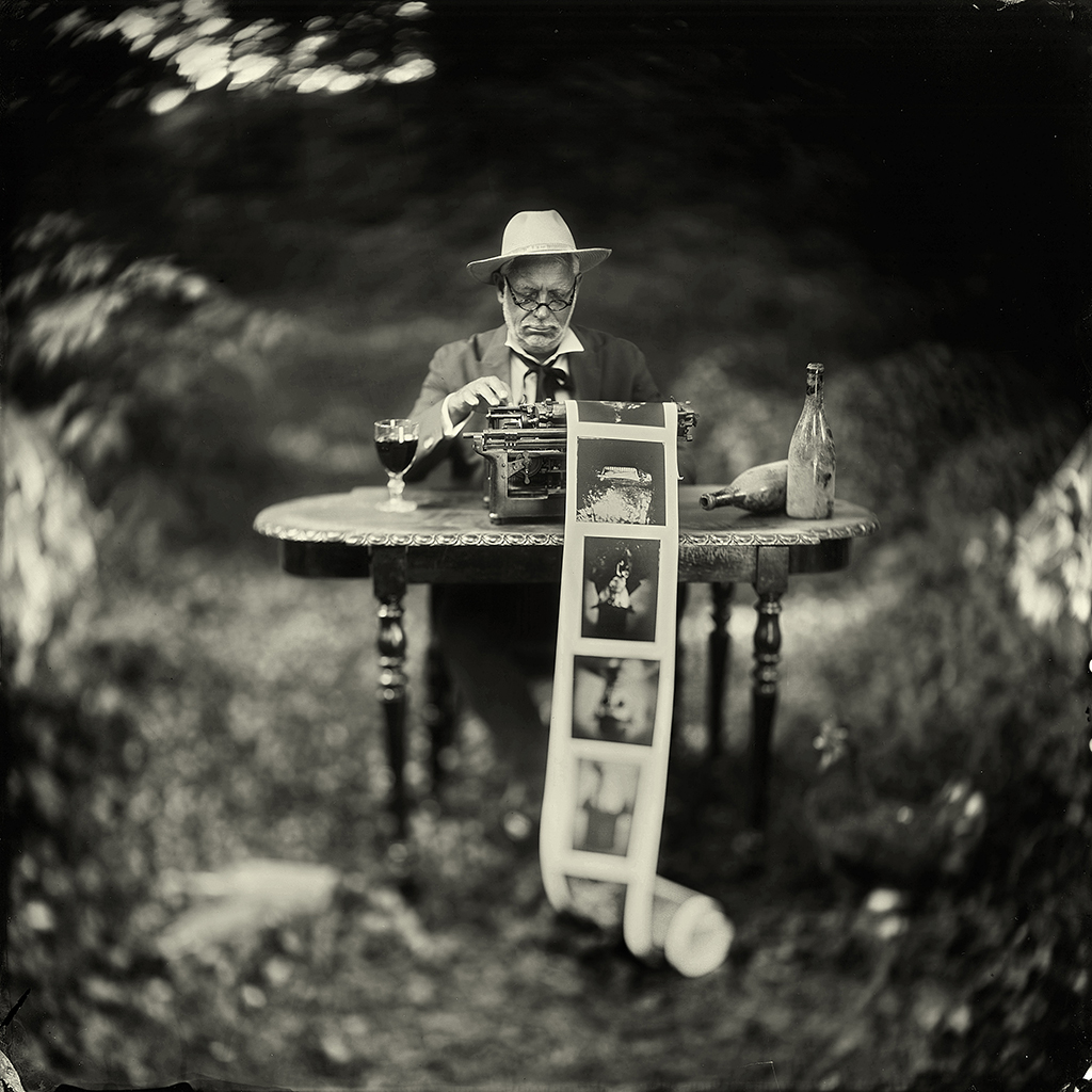 Wet-plate print of man sat at a table with typewriter by Alex Timmermans